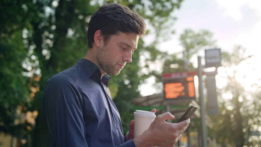 A young man sitting on a white bench in the park and using a phone. Medium shot | Shutterstock HD Video #31097743