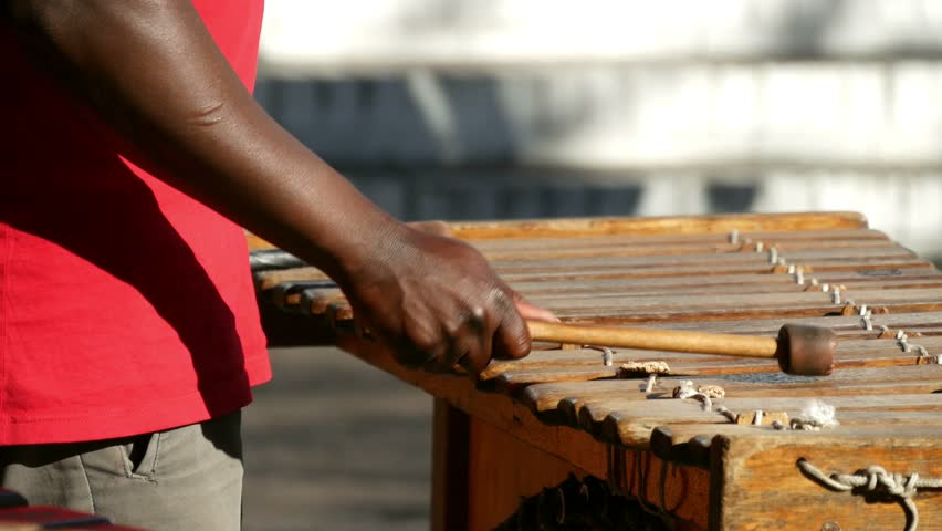 Close up of slight above view of wooden xylophone bars with dark skinned arms & hand rhythmically hitting the bars with out of focus passing people behind.