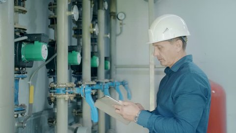 engineer inspects the gas boiler