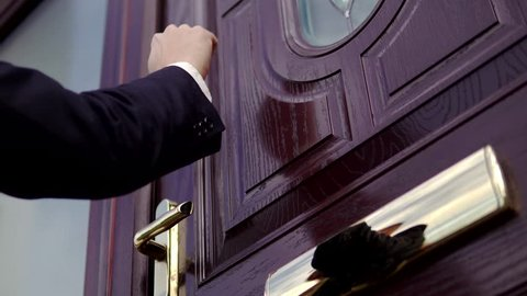 Man Knocks on Home Door in Suit, Waiting for Homeowner at Front. White Caucasian Professional.