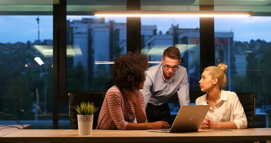 Diverse business people working in modern office late at night discussing strategy using computer   Shutterstock HD Video #31132336