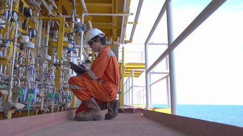 Offshore oil and gas business, production operator logging data and adjusting corrosion inhibitor pump to optimize flow for maintain gases and crude oil quality then report to control room by radio