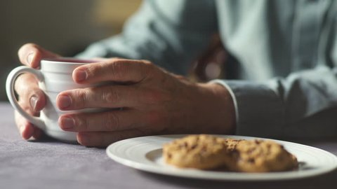 Elderly hand clasps tea mug, dunks and eats a cookie.