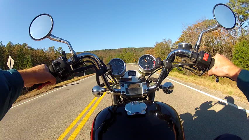 The point of view of a motorcycle rider on a rural road in South Eastern Oklahoma on a sunny autumn day.
