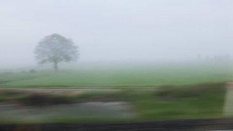 Fog over fields and forests trees as seen from the fast TGV train departing from Paris, France