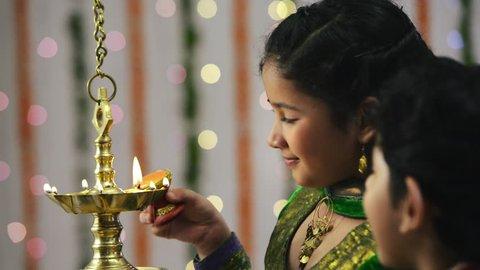 Locked-on shot of two children lighting an oil lamp during Diwali festival