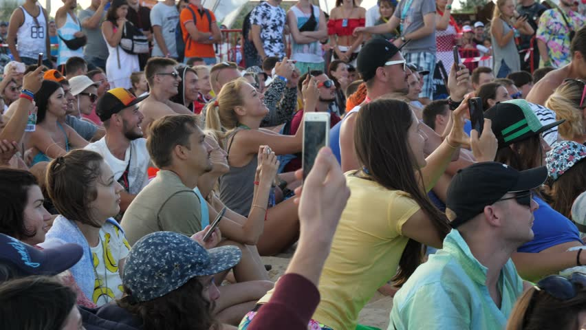 ZATOKA near ODESA, UKRAINE - AUG 24, 2017: Young People Crowd Sit By Stage Raise Mobile Phones Over Heads Shoot Video Of Public Concert Performance