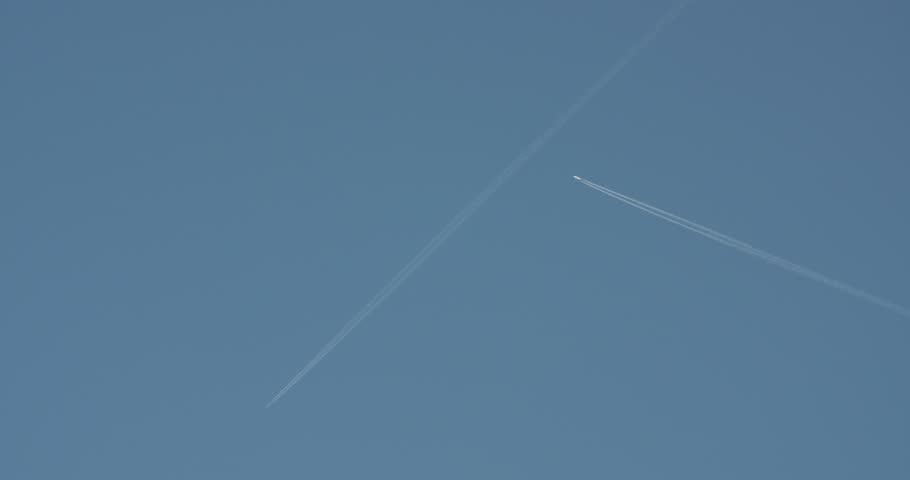 A distant airplane passes high overhead, leaving a jet contrail against a clear blue sky.