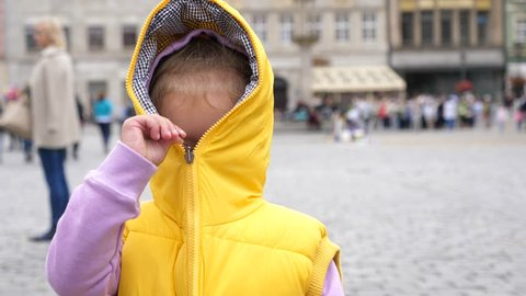 Little Kid Girl Have Fun Playfully Hiding Closing A Zipper Of Yellow Sleeveless Jacket With A Hood