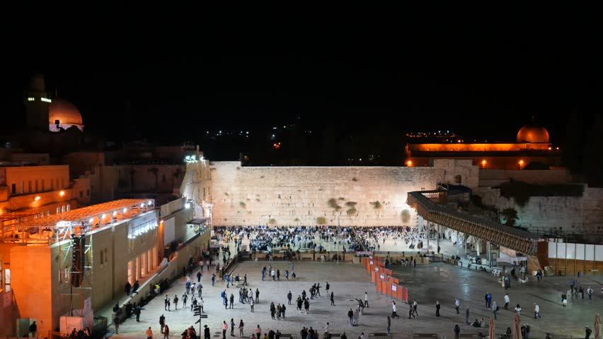 Timelapse of the western wall - the prayer plaza at midnight filled with religious Jewish people praying