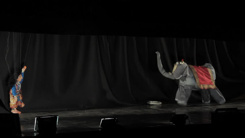 Marionette string puppets dance on a stage
