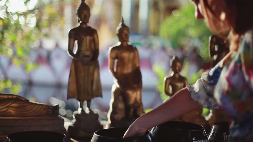 Set of Golden Buddha and the light of the sun. The Buddha Memorial Park. Woman donate. 1920x1080