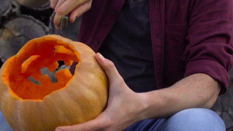 Man carves from a pumpkin Jack-o'-lantern in the backyard on a tree stump