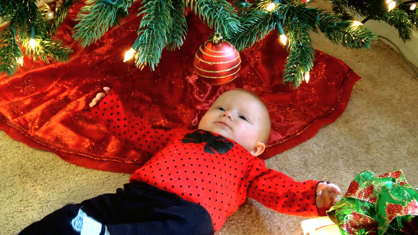 A Baby Underneath A Christmas Tree Is Fascinated By The Ornaments ...
