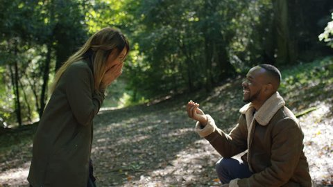 Young couple in the woods walk before the man makes a marriage proposal