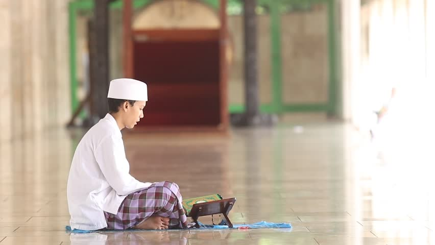 Video footage of a young muslim man wearing islamic clothes and sitting in the mosque while reading the holy Quran