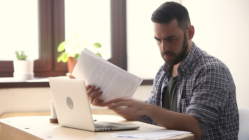 Stressed unmotivated man confused by mistake in documents, looking through papers, frowning using laptop, failing urgent task, missing deadline, quits after bad work fed up with difficult job | Shutterstock HD Video #31313923