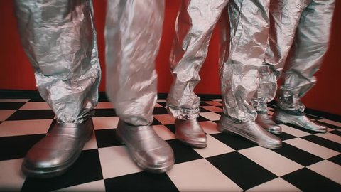 Tree pair of legs in silver galoshes and tin foil pants stomp on checkered tiled floor in rhythm in red walls room