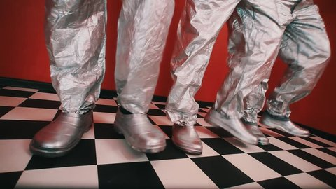 Tree pair of feet in silver galoshes and tin foil pants stomp on checkered tiled floor in rhythm in red walls room