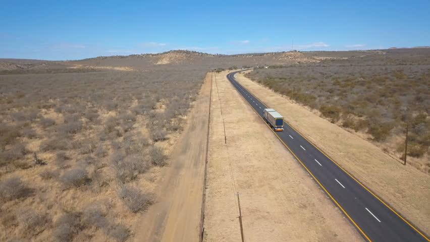 Semi truck and pickup truck rounding a bend in barren asphalt road aerial