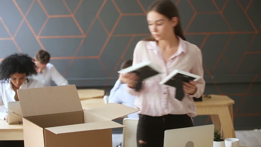 Fired young sad woman packing box standing near work desk, taking all her belongings after being dismissed resignation, upset employee quits from job collecting personal stuff at workplace to leave
