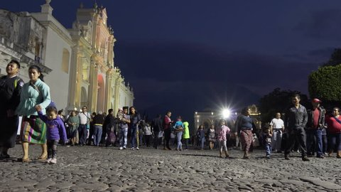 CIRCA 2010s - Antigua, Guatemala - POV shot of people walking at night along a busty street in front of the cathedral in Antigua, Guatemala.