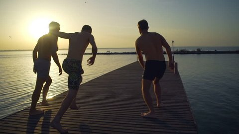 Group of friends running and jumping off sea pier in the water rapid slow motion