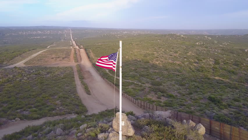 CIRCA 2010s - U.S.-Mexico border - The American flag flies over the U.S. Mexico border wall in the California desert. | Shutterstock HD Video #31373743