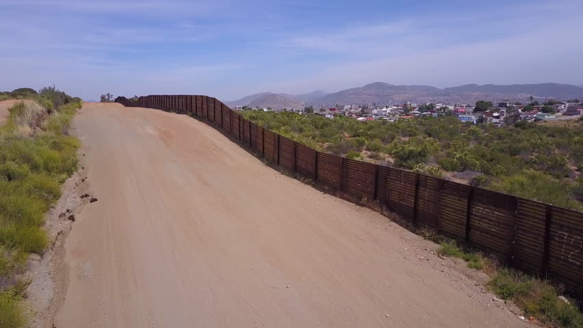 CIRCA 2010s - U.S.-Mexico border - Slow rising aerial along the U.S Mexican border wall fence reveals the town of Tecate Mexico. | Shutterstock HD Video #31374013