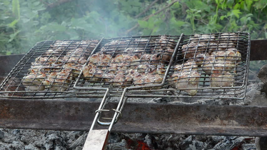 Shashlik fresh meat baked in metal grid on fireplace fire charcoal ember cinder heat.