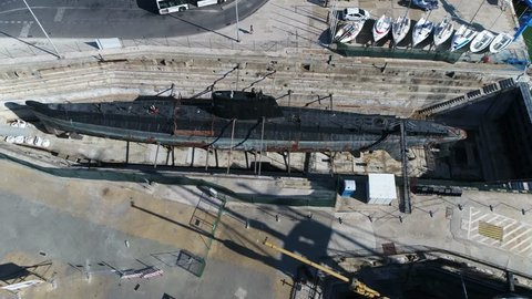 Aerial top-down view of submarine in empty dry dock used for construction maintenance and repair of several watercraft submarine is of small class and in port because of repair and maintenance of ship