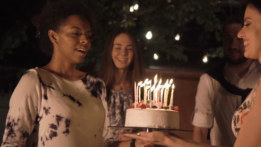 Cheerful Men And Women Celebrating With Cake Candles In Backyard