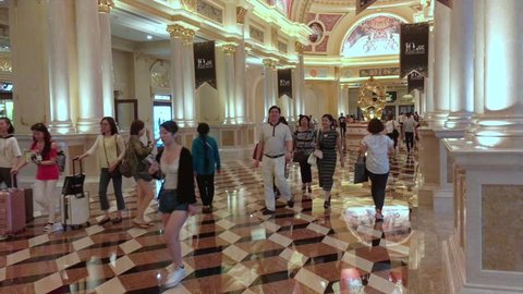 MACAU, CHINA - SEPT 15, 2017: Tourists walk at the Parisian hotel hall. Macaus gaming revenue has been the worlds largest since 2006 with the economy heavily dependent on gaming and tourism