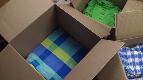 Man packs clothes, folded shirts, sweaters, towels, linen in boxes for donation or moving. 4K UHD 3840x2160