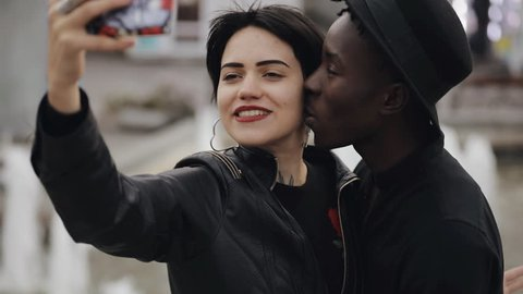 Slow motion of white woman and black man couple making a selfie video on smartphone. He kiss her cheek. They smiling, laughing together.