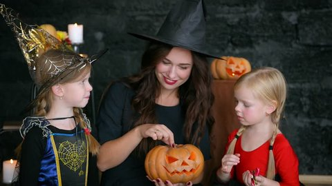 Little girls, little witches celebrate Halloween. Eat and scatter sweets. On a black background. jack lantern