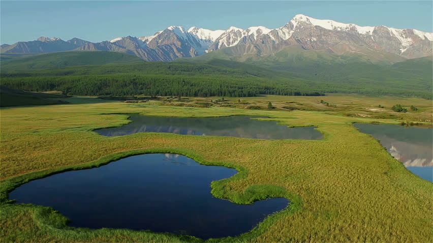 Aerial View. Flying over the beautiful lake near mountains. Aerial camera shot. Landscape panorama. Altai, Siberia.