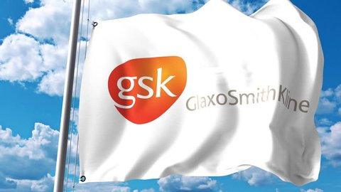 Waving flag with GlaxoSmithKline GSK logo against clouds and sky. 4K editorial animation