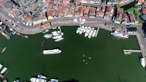 Aerial footage above small fishing town Volendam showing boats moving into small harbor and white swans flying over marina top-down view looking down onto popular tourist destination in Netherlands 4k