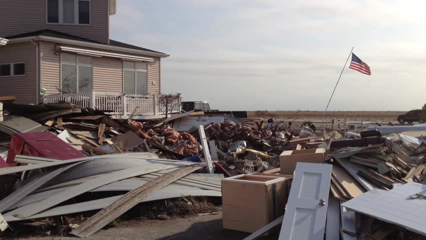 BREEZY POINT, QUEENS, NY-December 2, 2012: Footage clip of homes destroyed by waves and storm surge from Hurricane Sandy. Video pans across wreckage of destroyed homes, ends with image of U.S. Flag