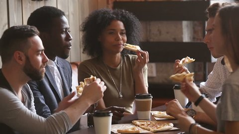 Multiracial happy young people eating pizza in pizzeria, black and white cheerful students enjoying meal dining sitting together at restaurant table, diverse hungry friends sharing lunch at meeting
