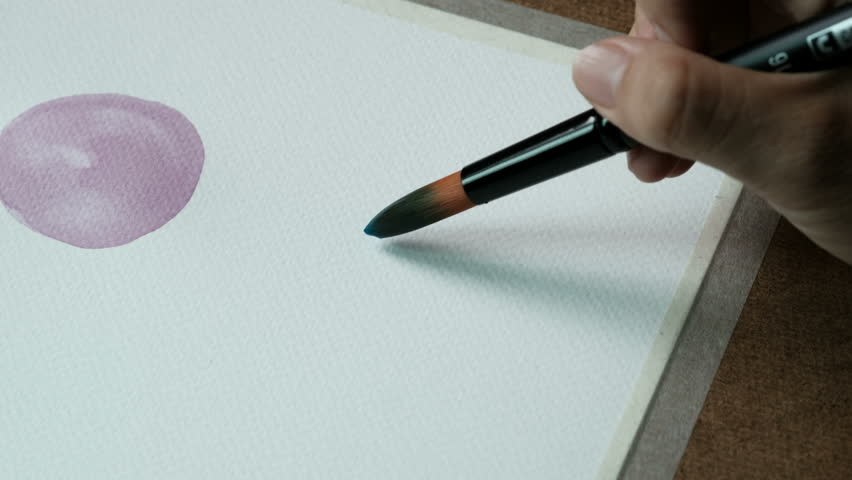 Closeup shot of artist's painting a blue circle in watercolors using a paintbrush on watercolors paper 300 GSM.    Shutterstock HD Video #31526713