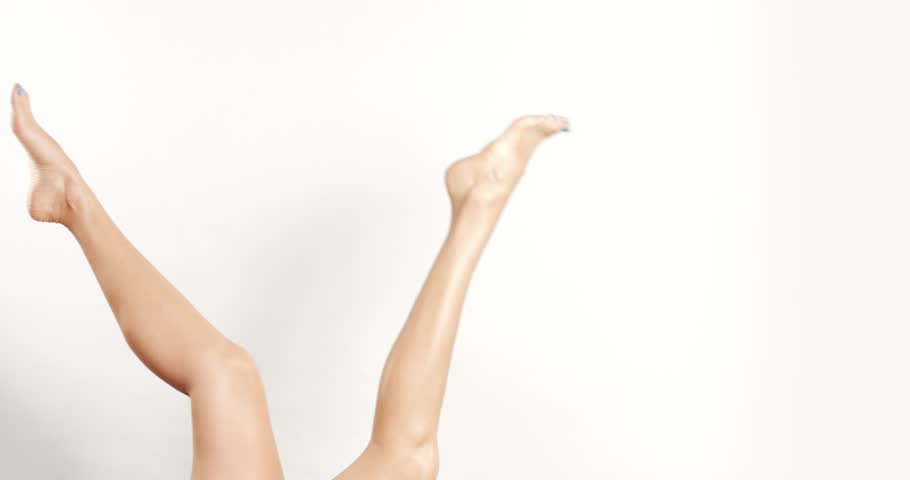 Attractive slim woman's legs up in the air on white background, doing some leg exercises