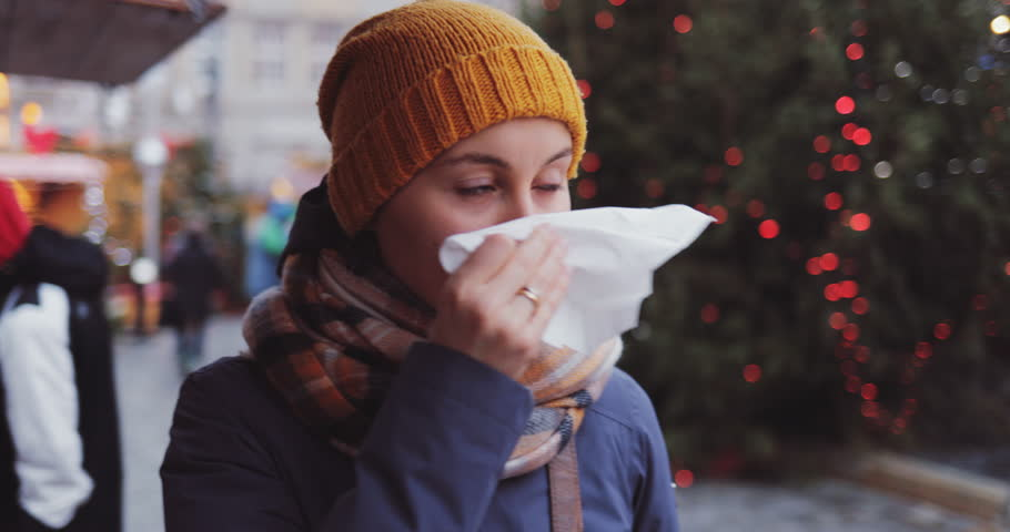 Sick Woman Blowing Her Nose Into Tissue Outdoors. SLOW MOTION 4K DCi. Young Female having cold or flu symptoms, standing in a busy city street. Autumn or winter cold weather.