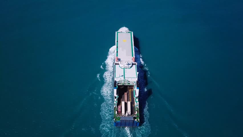 Aerial footage of a large Roro ship at sea. Roll-on/roll-off (RORO) ships are vessels designed to carry wheeled cargo, such as cars, trucks and railroad cars.