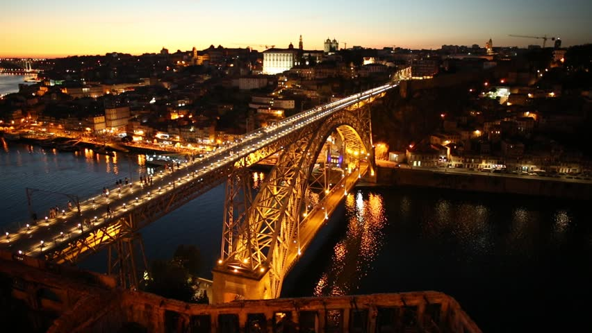 Aerial view of Oporto skyline and Ribeira Waterfront from Dom Luis I Bridge at twilight. Picturesque urban cityscape of Porto in Portugal. Tourist boats cruising on Douro River at sunset light.