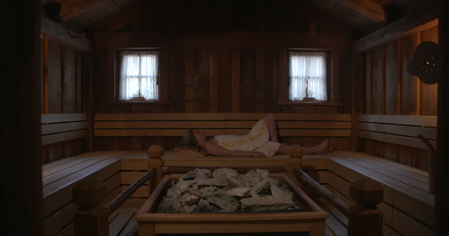 4k Back of young woman wrapped in sheet entering in spacious sauna