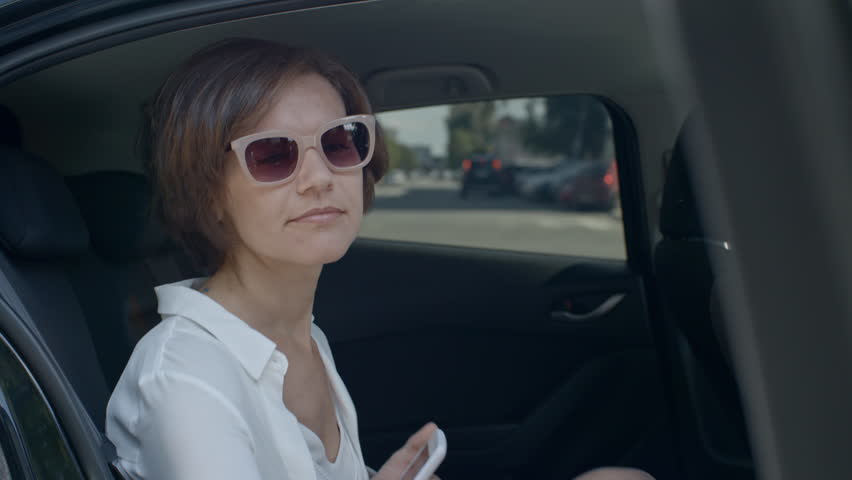 Attractive business lady in sunglasses holding smartphone while sitting on backseat and closing car door