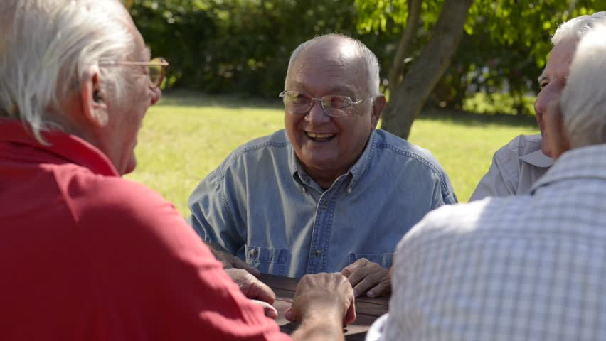 Active Retired Senior People, Old Friends And Leisure, Group Of Four Elderly Men Having Fun, Laughing And Talking In City Park. Sequence Of Medium And Wide ...