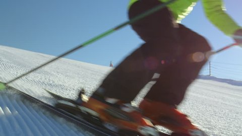 SLOW MOTION CLOSE Young adult skier in bright green jacket carving fast on excellent groomed ski piste in sunny winter day while doing fast slalom turns down the slope. Passing close to the camera